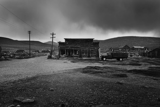 Old building exterior with stormy sky and truck in Bodi, California ghost town
