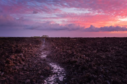 Hawaii, lava rock field with colored clouds and sunset between Mahai'ula Beach and Makalawena Beach